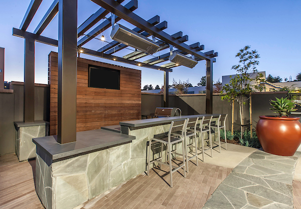 Outdoor BBQ area with breakfast bar and chairs.