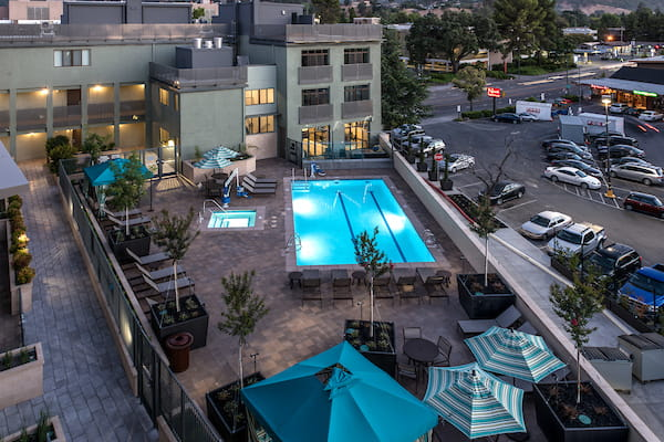 Aerial view of outdoor spa and swimming pool area with sundeck and lounge seating at dusk.