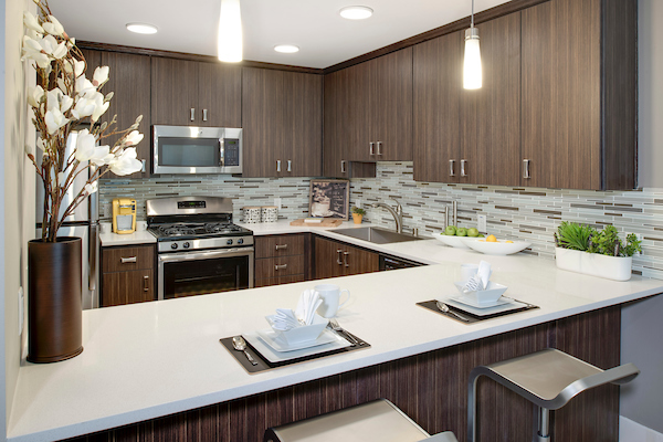 Staged kitchen with breakfast bar seating, quartz counter tops and stainless steel appliances.