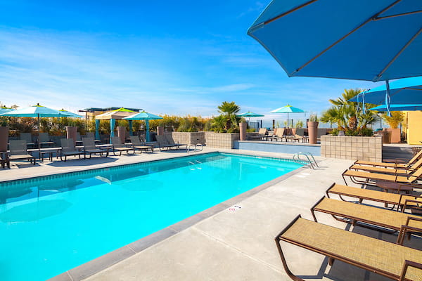 Outdoor swimming pool area with sundeck, lounge seating, and umbrellas.
