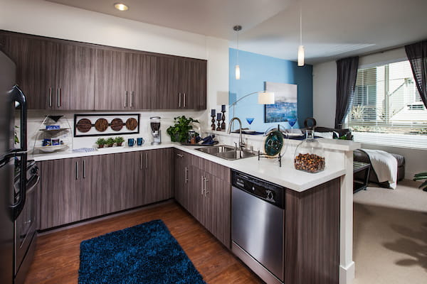 Staged kitchen with stainless steel appliances and hardwood-style vinyl flooring overlooking staged living room.