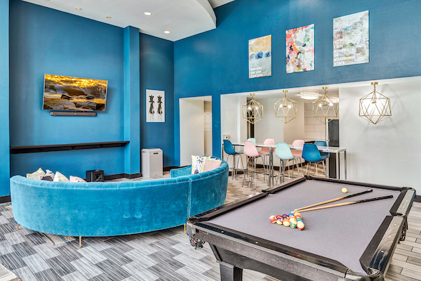 Clubhouse with pool table, sofa, TV, and high ceilings.