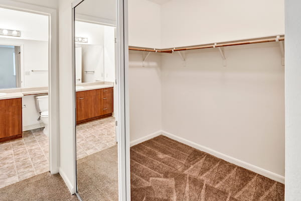 Sliding mirrored door closet with shelving and rack next to bathroom with tile flooring.