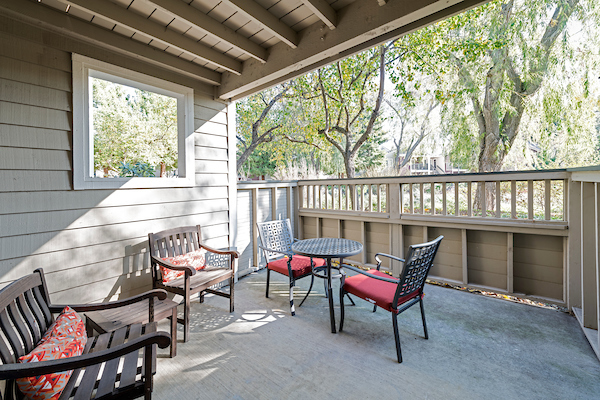 Apartment home patio with table and chairs.