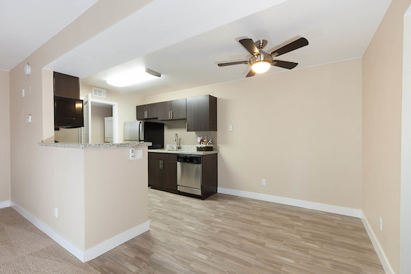 Kitchen with stainless steel appliances adjacent to dining area with ceiling fan.