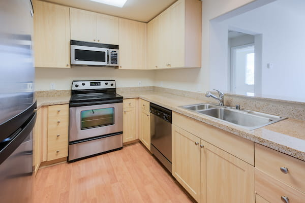 Kitchen with stainless steel appliances and hardwood style vinyl flooring.