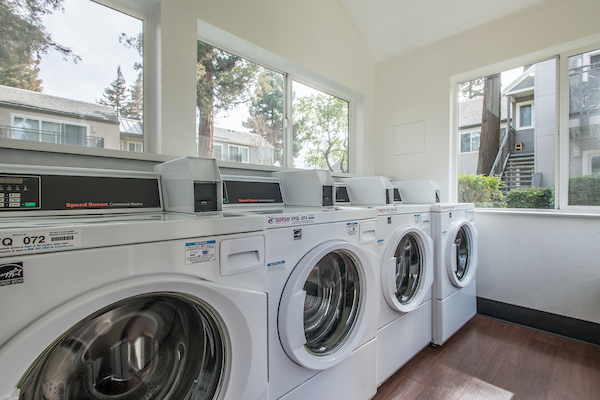 On-site community laundry room with four washing machines.