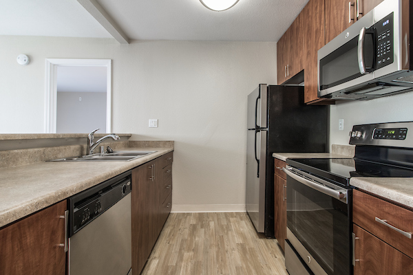 Kitchen with stainless steel appliances, quartz countertops, and hardwood-styled vinyl flooring.