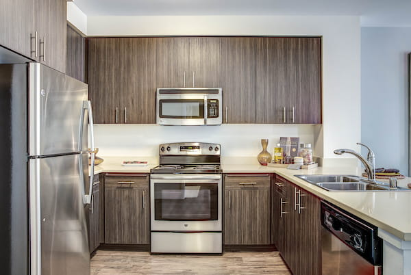Staged kitchen with hardwood-style flooring and stainless steel appliances.