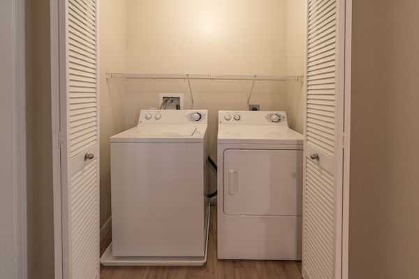 In-home washer and dryer in closet with shelving.