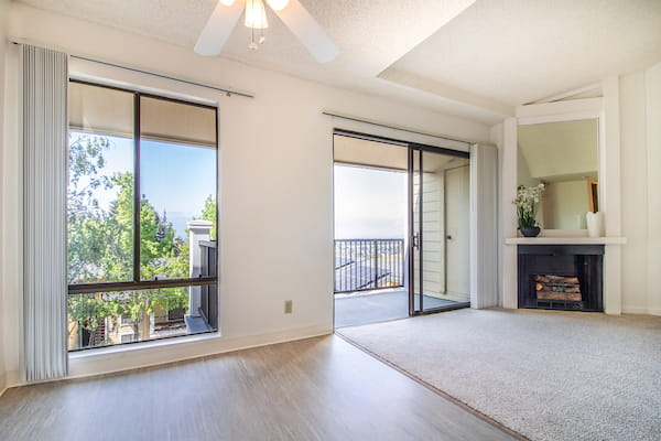 Living room with carpeting, fireplace, and sliding doors leading to balcony.