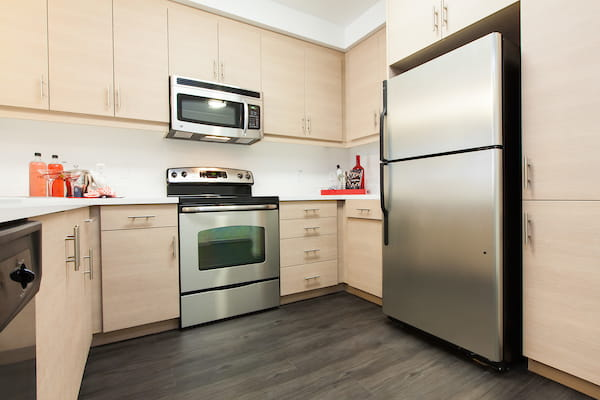Kitchen with stainless steel appliances and hardwood-style flooring.
