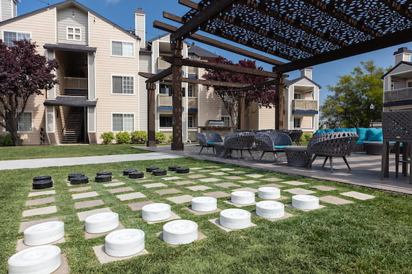 BBQ area under pergola with lounge seating adjacent to lawn area with over-sized checkers.