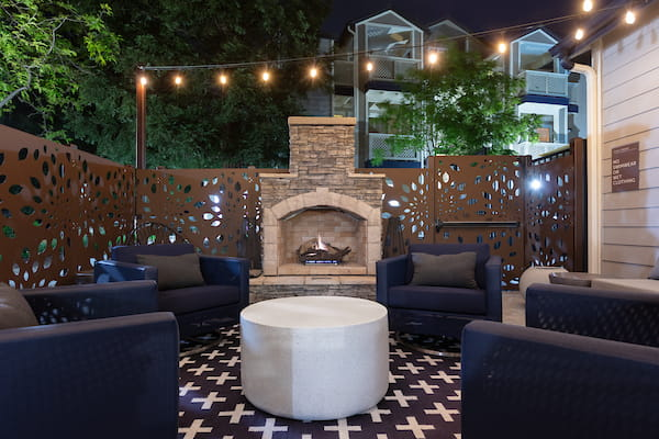 Fireplace surrounded by lounge seating at night.