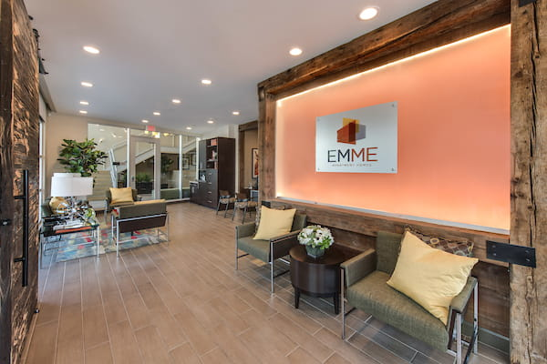 Resident lounge with Emme Apartment Homes sign on wall.