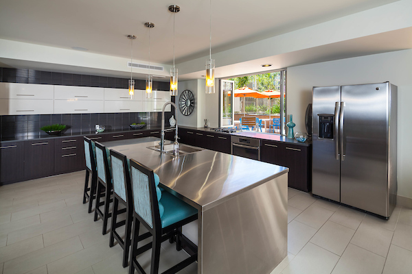 Clubhouse kitchen with stainless steel appliances and island seating.