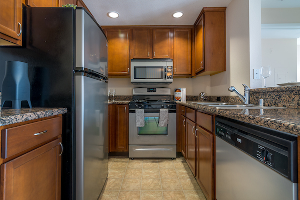 Kitchen with gas stove, granite countertops, and hard flooring.