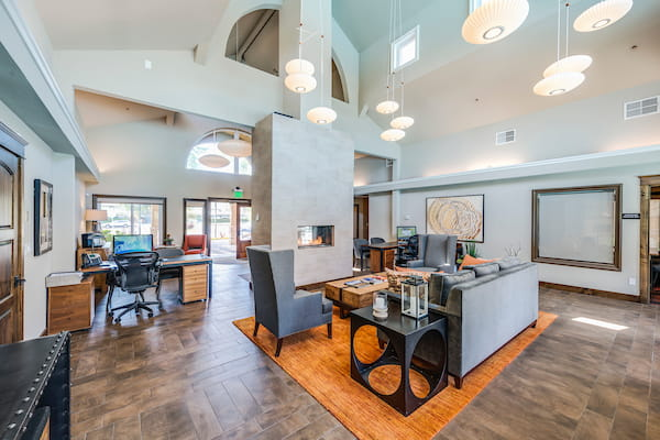 Leasing office with hardwood style flooring, high ceilings, fireplace, and lounge seating.