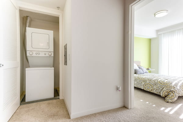 In-home washer and dryer in closet near staged bedroom.