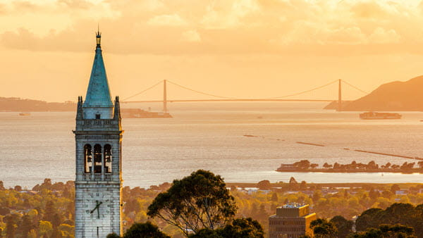 Berkeley's Sather Tower with view of bay and bridge in background.