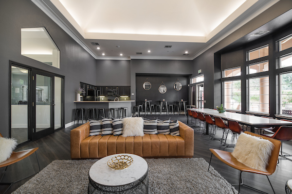 Clubhouse with hardwood style flooring, lounge seating, kitchen with bar seating, and high ceilings.