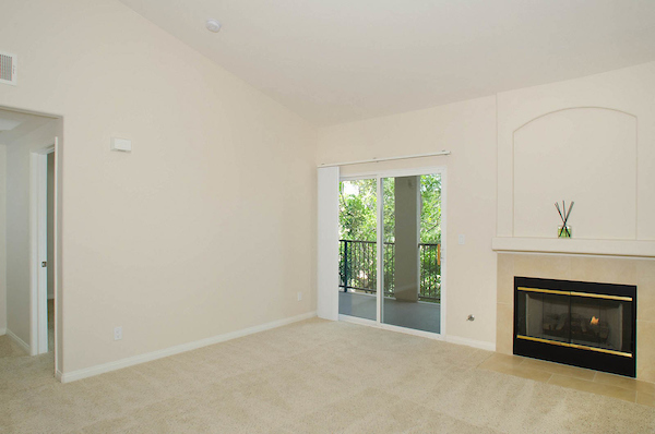 Living room with fireplace and sliding door leading to balcony.