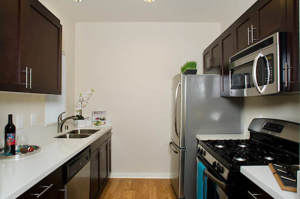 Staged galley kitchen with stainless steel appliances, gas stove, and hardwood style flooring.
