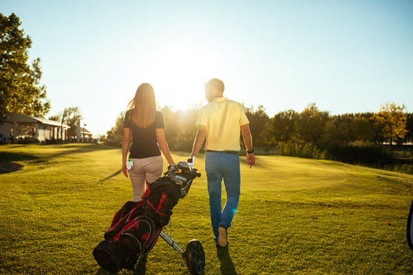 Woman and man with golf equipment walking on grass.