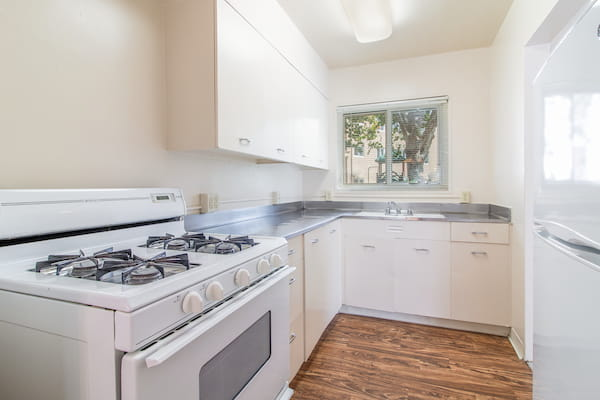 Classic kitchen with hardwood style flooring and gas stove.