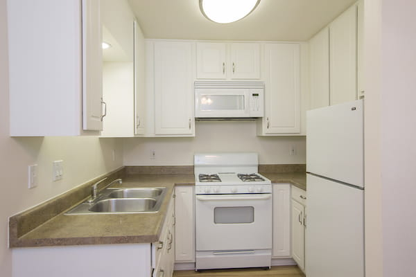 Class kitchen with gas stove and hardwood style flooring.