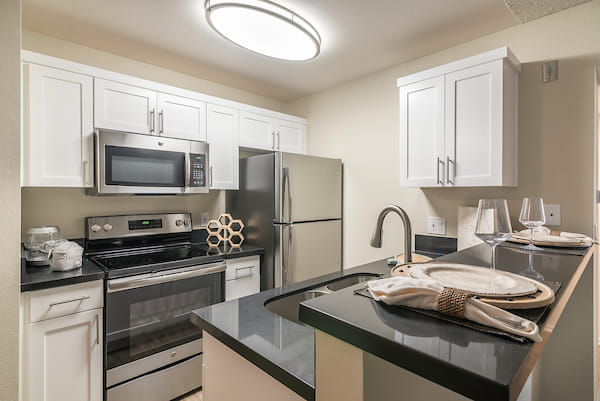 Staged kitchen with stainless steel appliances and breakfast bar.