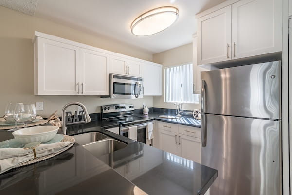 Staged kitchen with stainless steel appliances and window.