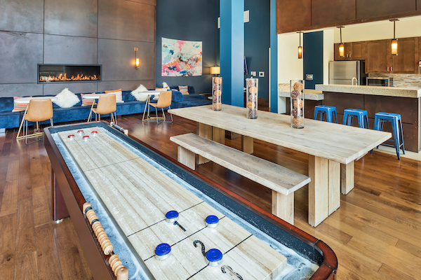 Clubhouse with kitchen, tables, chairs, and shuffleboard table.