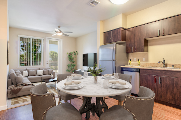 Open kitchen with stainless steel appliances adjacent to staged dining and living room.