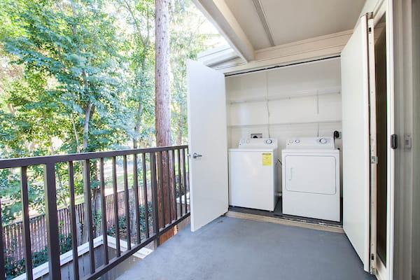 View of trees from an apartment home balcony with washer and dryer unit.