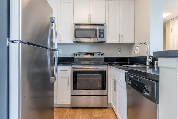 Kitchen with stainless steel appliances, hardwood style flooring, and quartz countertops.