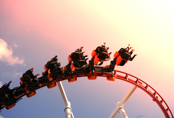 Roller coaster riders mid-air at sunset.