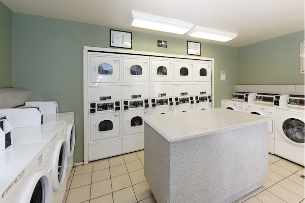 On-site laundry room with washers, dryers, and an island.
