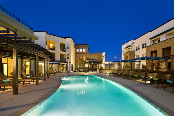 Outdoor swimming pool area with sundeck, lounge seating, pergola, and umbrellas at night.