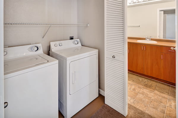 In-home washer and dryer unit adjacent to bathroom.