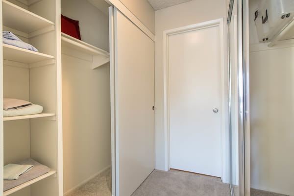 Sliding door closets with shelving and racks.