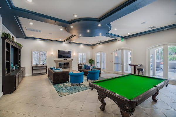 Clubhouse with fireplace, sofa, tables, lounge chairs, and pool table.