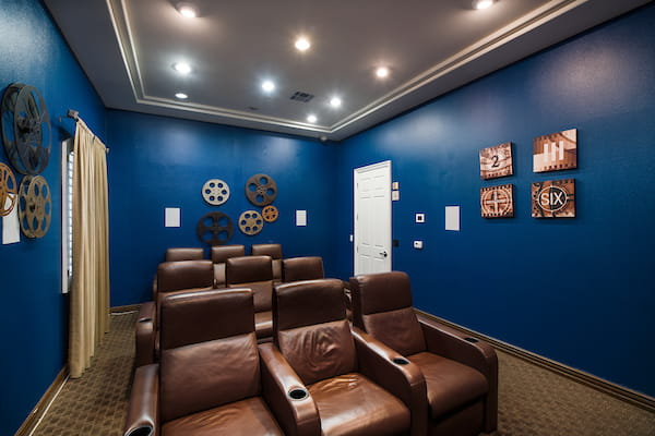 Theater room with TV and large arm chairs.