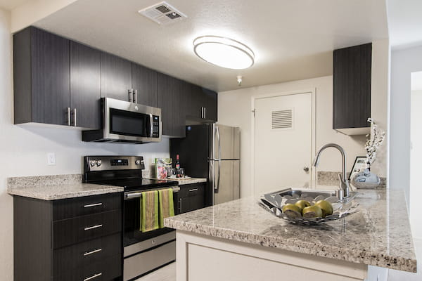 Staged kitchen with granite countertops, stainless steel appliances, and hardwood style flooring.