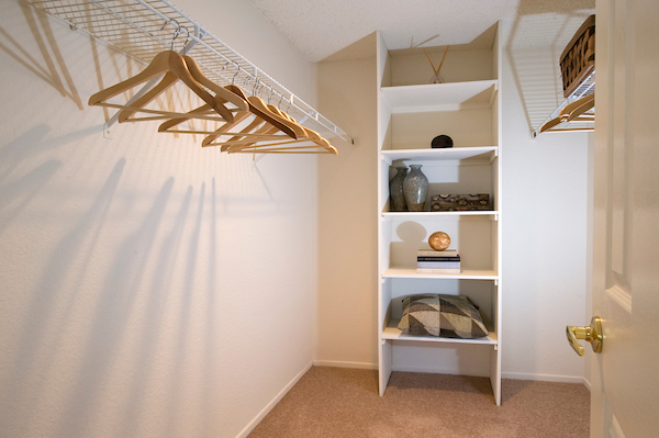Large staged walk-in closet with shelving and racks.