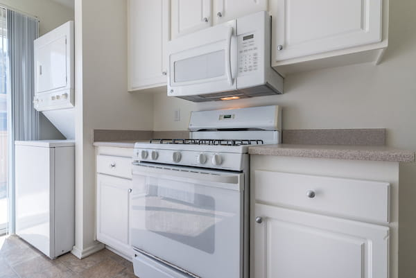 Classic kitchen with gas stove and in-home washer and dryer unit.