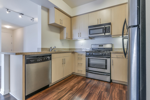 Kitchen with hardwood style flooring, gas stove, stainless steel appliances, and granite countertops.