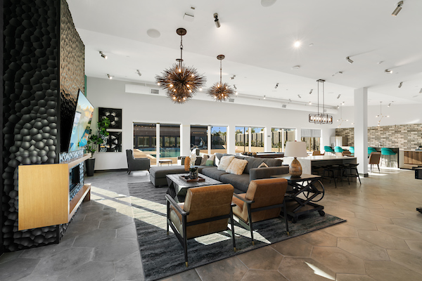 Clubhouse with TV, lounge chairs, and sliding doors leading to swimming pool area.