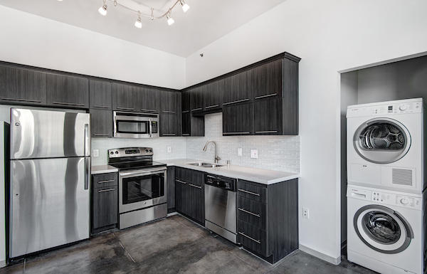 Kitchen with stainless steel appliances adjacent to in-home washer and dryer unit.