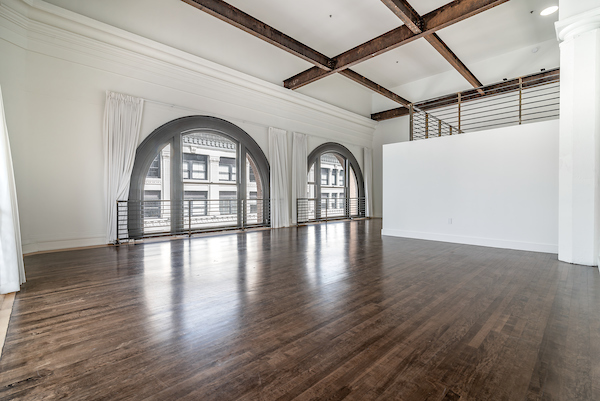 Penthouse with hardwood style flooring, large windows, and high ceilings.